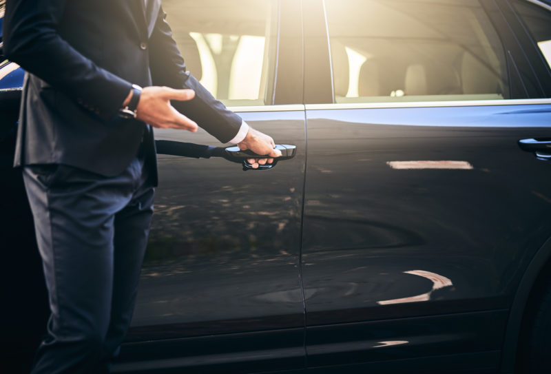 A Toronto Car Service driver opening the door to a limo